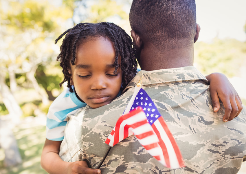 Child holding flag hugging military father