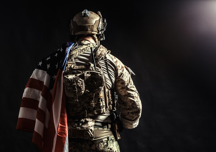 Soldier with flag draped around shoulder/back
