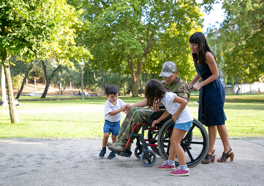 Soldier in wheelchair surrounded by kids and wife